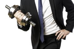 Businessman in black suit holding a silver dumbbell in the right hand